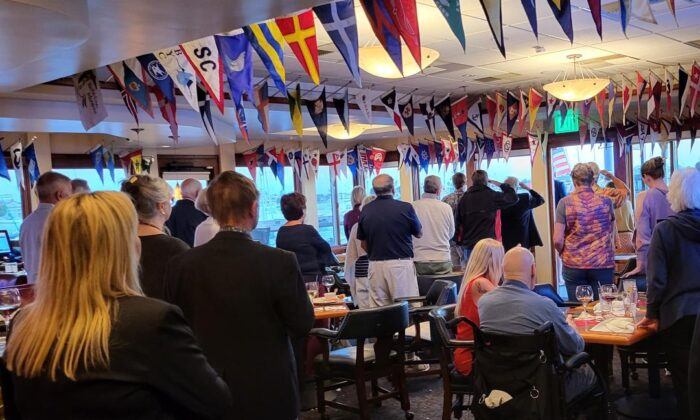 Members and guests of Bahia Corinthian Yacht Club stand in silence during a special Colors ceremony in honor of the 13 fallen soldiers who died on Aug. 23 during the American retreat from Afghanistan, in Newport Beach, Calif., on Sept. 15, 2021. (Lynn Hackman/The Epoch Times)