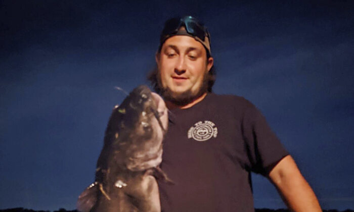 Ben Tomkunas holds a catfish he caught in Coventry, Conn., on Aug. 21, 2021. (Chris Braga via AP)