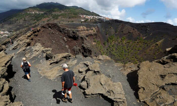 Tourists walk next to the crater of the San Antonio Volcano on the Canary Island of La Palma, Spain, on Sept. 17, 2021. (Borja Suarez/Reuters)