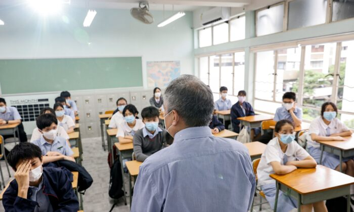A teacher introduces himself to the students in a classroom at a secondary school, during the first day of the new term, in Hong Kong on Sept. 1, 2021. (Tyrone Siu/Reuters)
