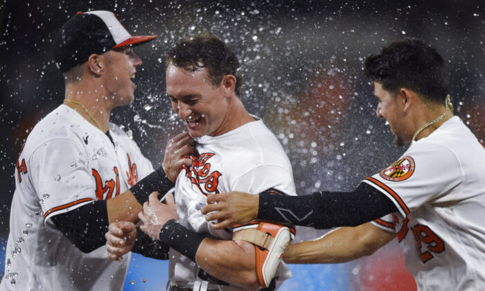 Baltimore Orioles' Austin Hays (C) is congratulated by Ryan Mountcaste (L) and Ramon Urias (R) after driving in the winning run against the New York Yankees during the 10th inning of a baseball game in Baltimore, Md., on Sept. 16, 2021. (Gail Burton/AP Photo)