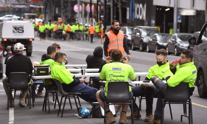 Construction workers take their lunch break on a busy street in Melbourne, to protest the closing of their onsite tea rooms by the state government, on Sept. 17, 2021. (William West/AFP via Getty Images)