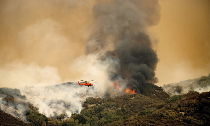 A helicopter prepares to drop water on the KNP Complex Fire in Sequoia National Park, Calif., Sept. 15, 2021. (Noah Berger/AP Photo)