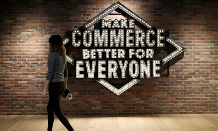 An employee walks past a sign at Shopify's headquarters in Ottawa, Ontario, Canada, on Oct. 22, 2018. (Chris Wattie/Reuters)