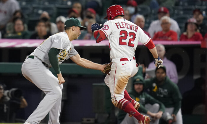 Los Angeles Angels' David Fletcher (22) is tagged out by Oakland Athletics first baseman Matt Olson during the seventh inning of a baseball game in Anaheim, Calif., on Sept. 17, 2021. (AP Photo/Ashley Landis)