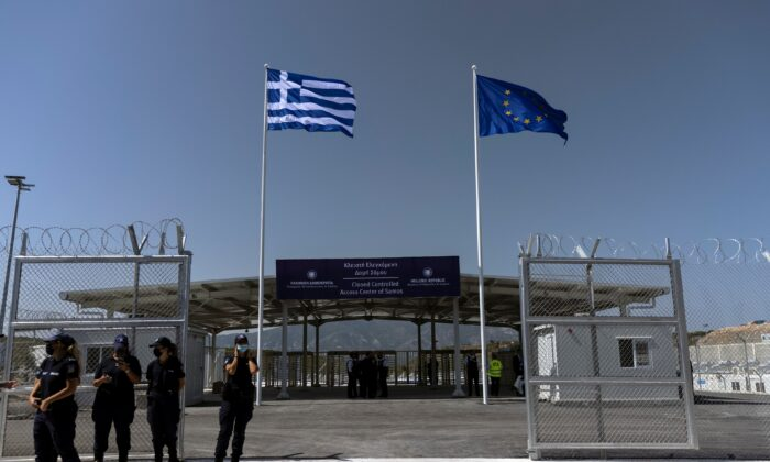 A Greek national flag and a European Union flag flutter inside a newly inaugurated closed-type migrant camp on the island of Samos, Greece, on Sept. 18, 2021. (Alkis Konstantinidis /Reuters)