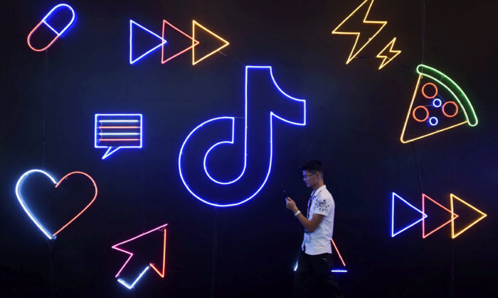A man holding a phone walks past a sign of Chinese company ByteDance's app TikTok, known locally as Douyin, at the International Artificial Products Expo in Hangzhou, Zhejiang Province, China, on Oct. 18, 2019. (Stringer/Files/Reuters)