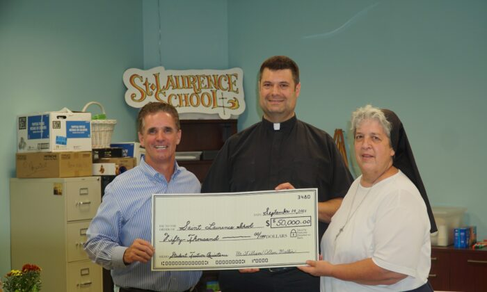 William Mullin (left) held the $50,000 check donated to St. Laurence School, with St. Laurence pastor Father Thomas Whittingham (middle) and Sister Regina Matulka, the school's principal. (Lily Sun/The Epoch Times)