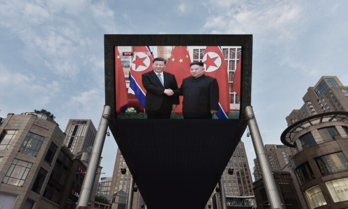 Chinese leader Xi Jinping (L) being greeted in Pyongyang by North Korean leader Kim Jong Un is shown on a large screen outside a shopping mall in Beijing on June 20, 2019. (Greg Baker/AFP)