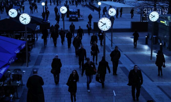 Workers walk to work during the morning rush hour in the financial district of Canary Wharf in London on Jan. 26, 2017. (Eddie Keogh/Reuters)