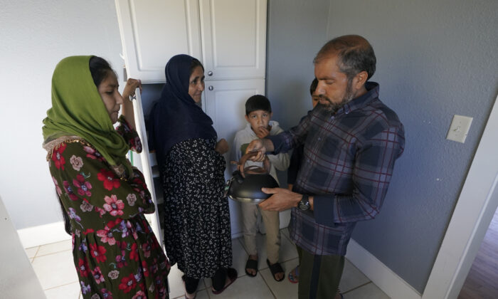 Abdul, right, who worked as a mechanic before he left Kabul, Afghanistan with his family about a month ago, shows his family a donated tea kettle as they stand in the kitchen of a rental house that has been provided as a place for them to stay in Seattle, Washington on Thursday, Sept. 16, 2021, (Ted S. Warren/AP Photo)
