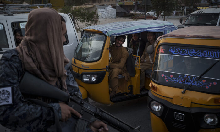 Afghan drivers and passengers stuck in a traffic jam look at Taliban fighters riding in the back of a pickup truck in Kabul, Afghanistan, on Sept. 20, 2021. (Felipe Dana/AP Photo)