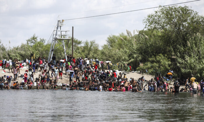Illegal immigrants bathe and play on the U.S. side of the Rio Grande, the international boundary with Mexico, in Del Rio, Texas, on Sept. 18, 2021. (Charlotte Cuthbertson/The Epoch Times)