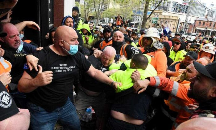 Construction workers clash with unionists at a protest at Construction, Forestry, Maritime, Mining and Energy Union (CFMEU) headquarters in Melbourne, Monday, Sept. 20, 2021. (AAP Image/James Ross)