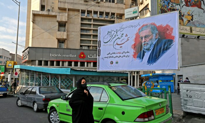A woman walks by a billboard honoring slain nuclear scientist Mohsen Fakhrizadeh in the Iranian capital Tehran, on Nov. 30, 2020. (Atta Kenare/AFP via Getty Images)
