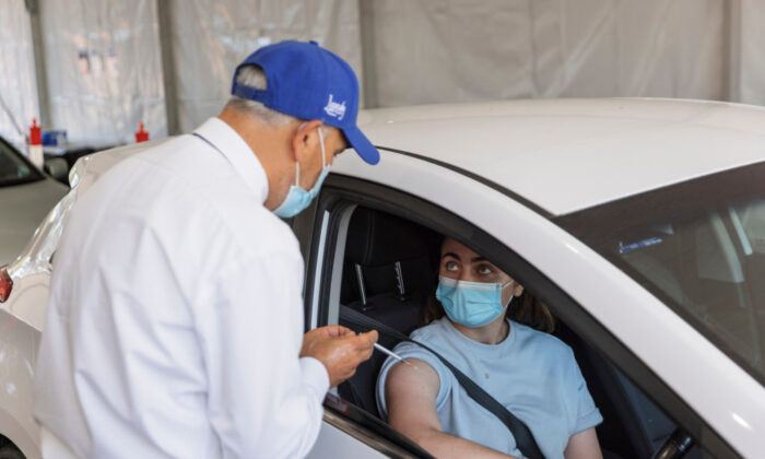 Dr Jamal Rifi administers a COVID-19 vaccine at a new drive-through vaccination clinic at Belmore Sports Ground in Sydney, Australia, on Sept. 17, 2021. (Brook Mitchell/Getty Images)