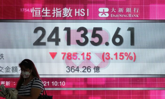 A woman walks past a bank's electronic board showing the Hong Kong share index at Hong Kong Stock Exchange in Hong Kong on Sept. 20, 2021. (Vincent Yu/AP Photo)