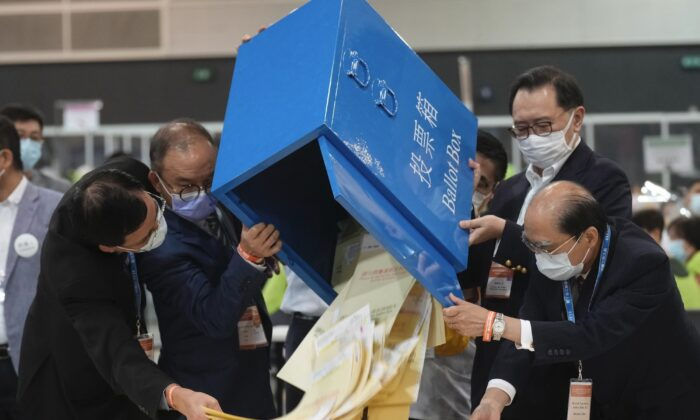 Erick Tsang (2nd L) Secretary for Constitutional and Mainland Affairs Bureau, helps officials in pouring out ballots from a box at a counting center in Hong Kong, on Sunday, Sept. 19, 2021. (Vincent Yu/AP Photo)