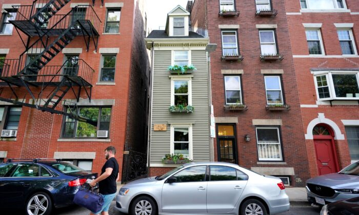 A man walks by Boston's famous Skinny House (at center) in Boston, Mass., on Aug. 13, 2021. (Elise Amendola/AP Photo)