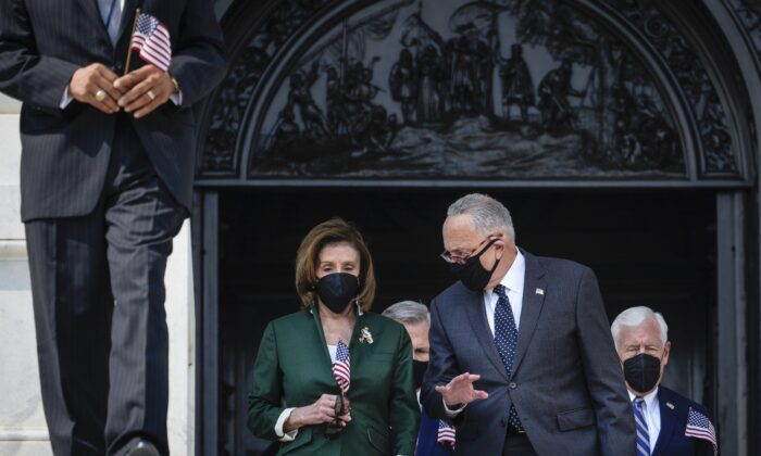 (L-R) Speaker of the House Nancy Pelosi (D-Calif.) and Senate Majority Leader Chuck Schumer (D-N.Y.) talk with each other as they walk down the steps of the U.S. Capitol  in Washington on Sept. 13, 2021. (Drew Angerer/Getty Images)