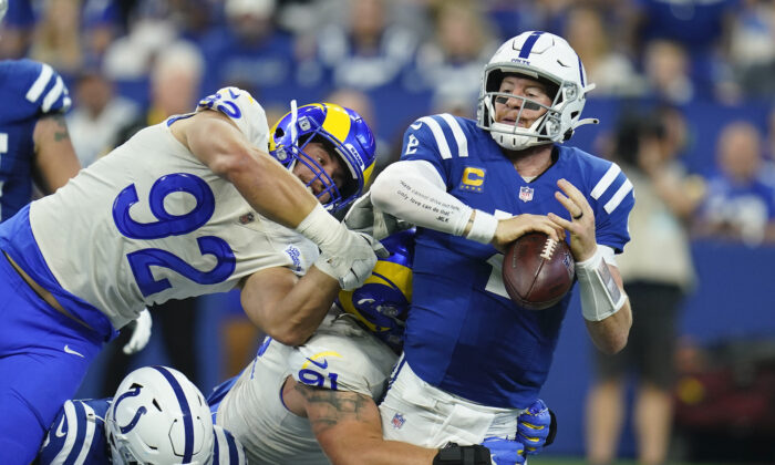 Indianapolis Colts quarterback Carson Wentz (2) is sacked by Los Angeles Rams' Greg Gaines (91) during the first half of an NFL football game in Indianapolis on Sept. 19, 2021. (AP Photo/Michael Conroy)