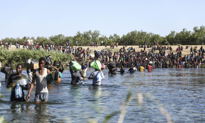 Illegal immigrants cross the Rio Grande between Del Rio (far side) and Acuna, Mexico. Some are crossing back to Mexico to avoid deportation from the United States, in Acuna, Mexico, Sept. 20, 2021. (Charlotte Cuthbertson/The Epoch Times)
