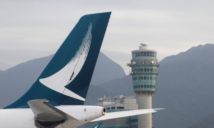 A Cathay Pacific jet is seen in front of air traffic control tower at the Hong Kong International Airport on Oct. 24 2020. (Tyrone Siu/Reuters)
