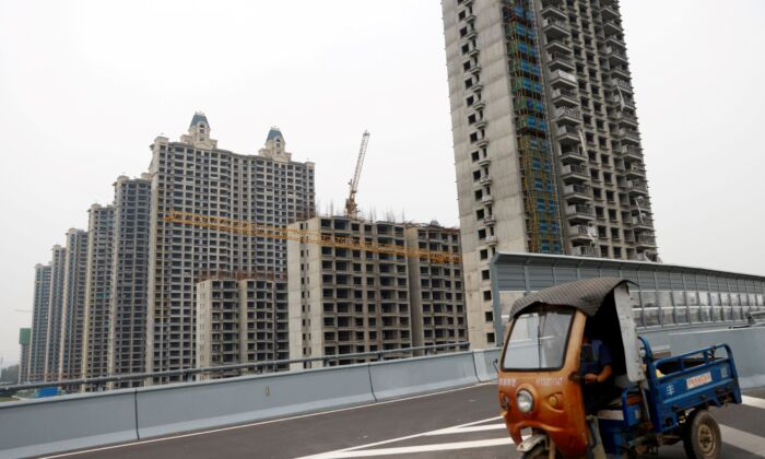 A vehicle drives past unfinished residential buildings at Evergrande Oasis, a housing complex developed by Evergrande Group, in Luoyang, China, on Sept. 16, 2021. (Carlos Garcia Rawlins/Reuters)