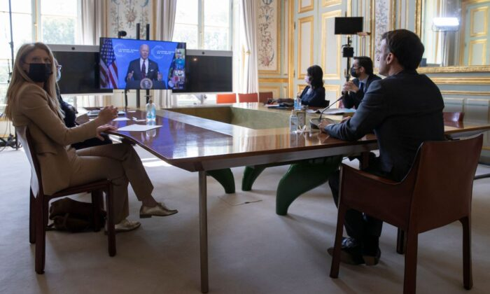 French President Emmanuel Macron listens to U.S. President Joe Biden (on screen) speak during a virtual Earth Day Climate Summit, video conference call, at the Elysee Palace in Paris on April 22, 2021. (Ian Langsdon/AFP via Getty Images)