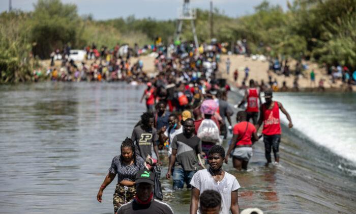 Illegal migrants cross the Rio Grande River near a temporary migrant camp under the international bridge on Sept. 18, 2021, in Del Rio, Texas. (Jordan Vonderhaar/Getty Images)