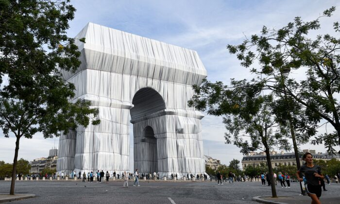 Bystanders walk near the Arc de Triomphe, wrapped in silver-blue fabric, as it was designed by late artist Christo, in Paris as part of the 38th European Heritage Days and the launch of the Cultural Olympiad in Paris, on Sept. 19, 2021. (Alain Jocard/AFP via Getty Images)