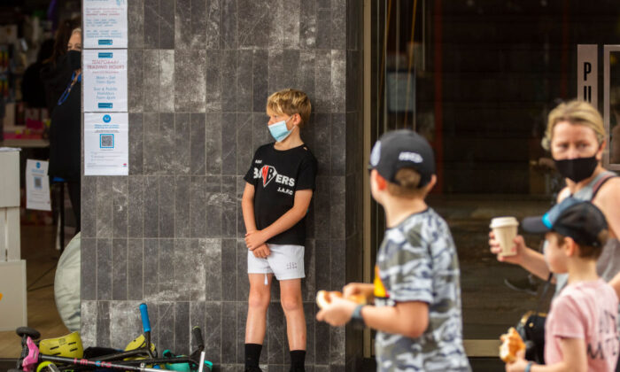 A boy wearing a mask stands at the front of a store in Manly, Sydney, Australia, on January 3, 2021. (Jenny Evans/Getty Images)