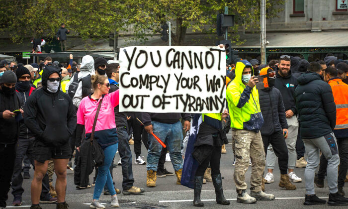 Protesters hold a sign that reads 'You cannot comply your way out of tyranny' during demonstrations against mandatory COVID-19 vaccines and restrictions in Melbourne, Australia, on Sept. 21, 2021. (Darrian Traynor/Getty Images)