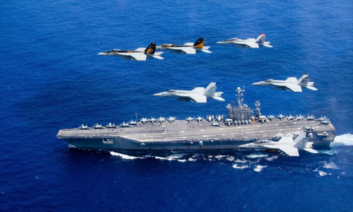 Aircraft pass in formation above the Nimitz-class aircraft carrier USS John C. Stennis in the Philippine Sea, on June 18, 2021. (Lt. Steve Smith/U.S. Navy via Getty Images)