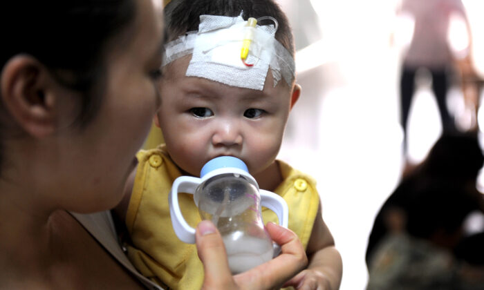 A woman feeds a baby who suffers from kidney stones after drinking tainted milk powder at the Chengdu Children's Hospital on September 22, 2008 in Chengdu of Sichuan Province, China.  (China Photos/Getty Images)