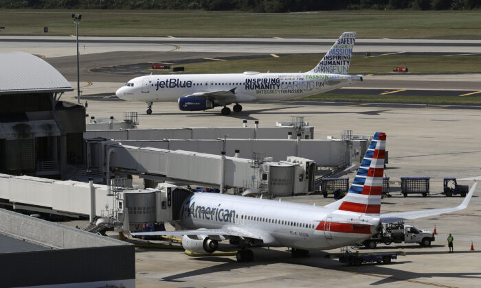 A JetBlue Airbus A320 taxis to a gate after landing, as an American Airlines jet is seen parked at its gate at Tampa International Airport in Tampa, Fla., on Oct. 26, 2016. (Chris O'Meara/AP Photo File)