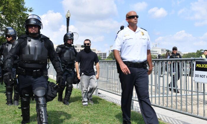A man later identified as a Customs and Border Protection Officer (C) is escorted by U.S. Capitol Police officers away from a rally in Washington on Sept. 18, 2021. (Eric Baradat/AFP via Getty Images)