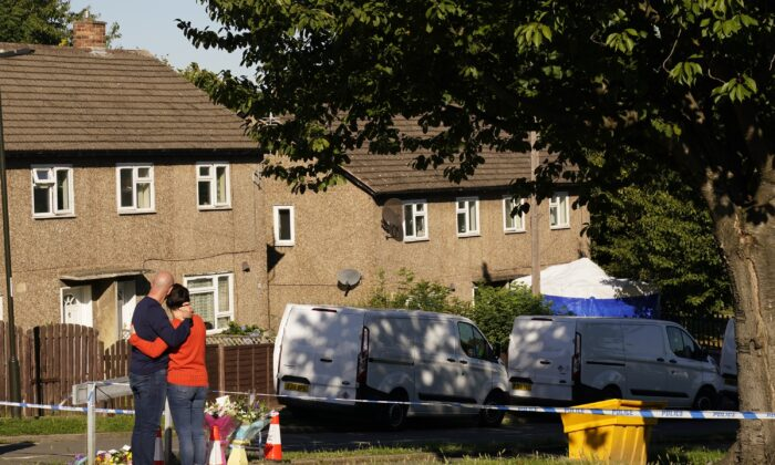 The father to some of the victims leaves flowers at the scene, where four people were found dead at a house on Sunday, in Chandos Crescent, Killamarsh, near Sheffield, England, on Sept. 20, 2021. (Danny Lawson/PA)