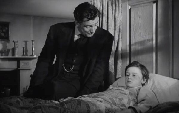 man talking to boy in sick bed