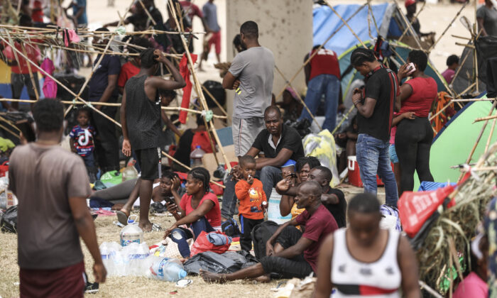 Thousands of illegal immigrants, mostly Haitians, live in a primitive, makeshift camp under the International Bridge, that spans the Rio Grande between the United States and Mexico, while waiting to be detained and processed by Border Patrol, in Del Rio, Texas, on Sept. 21, 2021. (Charlotte Cuthbertson/The Epoch Times)