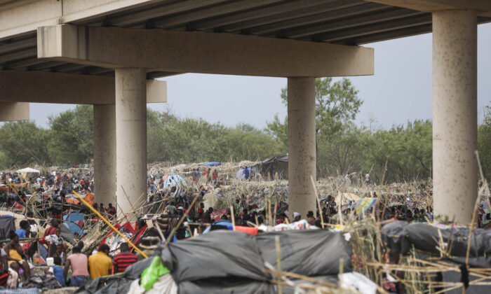 Thousands of illegal immigrants, mostly Haitians, live in a primitive, makeshift camp under the international bridge that spans the Rio Grande between the United States and Mexico while waiting to be detained and processed by Border Patrol, in Del Rio, Texas, on Sept. 21, 2021. (Charlotte Cuthbertson/The Epoch Times)