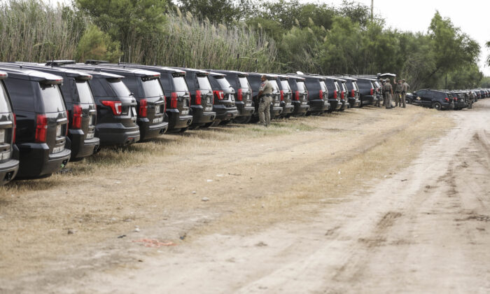 Texas State Police vehicles are lined up along the border as thousands of illegal immigrants, mostly Haitians, live in a primitive, makeshift camp under the International Bridge, which spans the Rio Grande between the United States and Mexico, while waiting to be detained and processed by Border Patrol, in Del Rio, Texas, on Sept. 21, 2021. (Charlotte Cuthbertson/The Epoch Times)