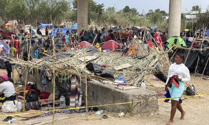 Thousands of illegal immigrants, mostly Haitians, live in a primitive, makeshift camp under the International Bridge that spans the Rio Grande between the United States and Mexico while waiting to be detained and processed by Border Patrol in Del Rio, Texas, on Sept. 21, 2021. (Charlotte Cuthbertson/The Epoch Times)