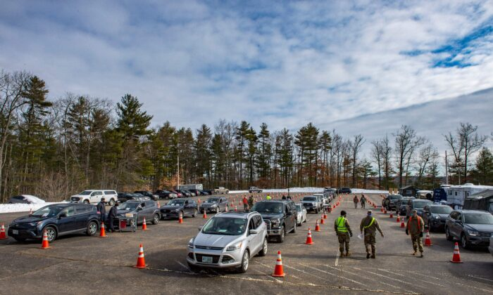 Servicemen coordinate people in their cars as they line up to be vaccinated at a vaccination center in Londonderry, N.H., on Feb. 4, 2021. (Joseph Prezioso/AFP via Getty Images)
