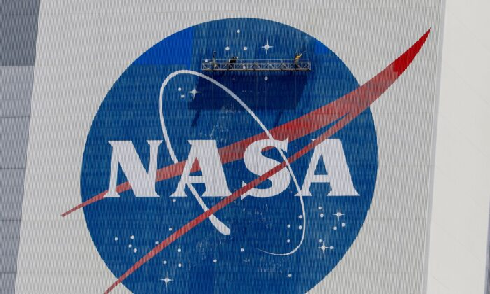 Workers pressure wash the logo of NASA on the Vehicle Assembly Building before SpaceX will send two NASA astronauts to the International Space Station aboard its Falcon 9 rocket, at the Kennedy Space Center in Cape Canaveral, Fla., on May 19, 2020. (Joe Skipper/Reuters)