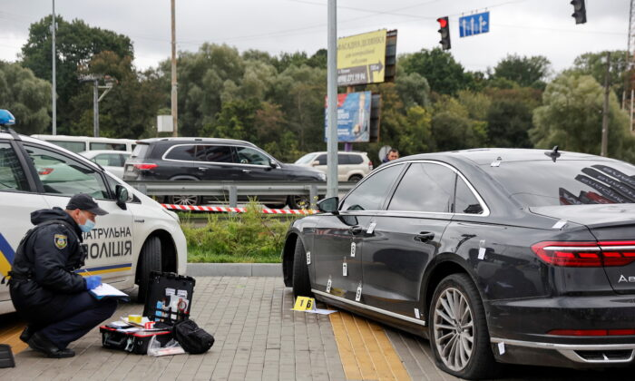 An investigator examines bullet holes in a car of Serhiy Shefir, Ukrainian President Volodymyr Zelensky's principal aide, following an assault outside of Kyiv, Ukraine, on Sept. 22, 2021. (Serhii Nuzhnenko/Reuters)