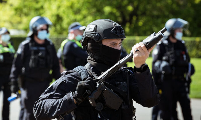 A riot police officer wields a weapon looking onwards at protesters near the Shrine of Remembrance, in Melbourne, Australia, on Sept. 22, 2021. (Darrian Traynor/Getty Images)