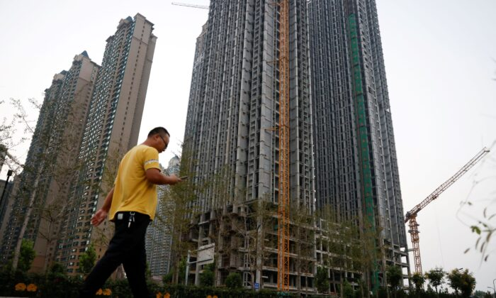 A man walks in front of unfinished residential buildings at the Evergrande Oasis, a housing complex developed by Evergrande Group, in Luoyang, China on Sept. 15, 2021. (Carlos Garcia Rawlins/Reuters)