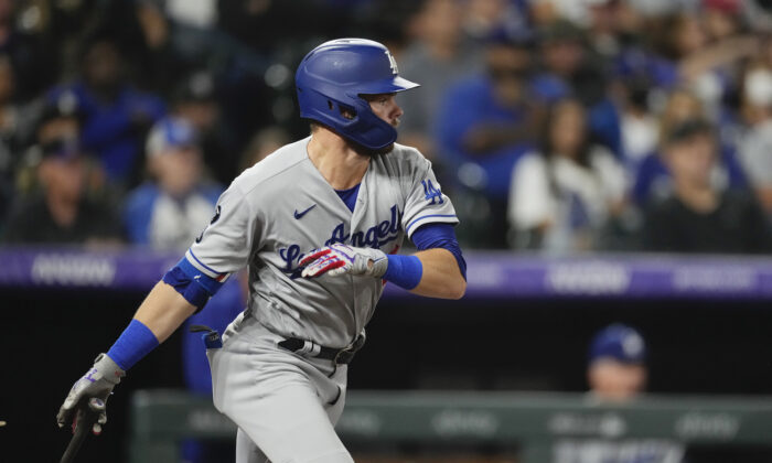 Los Angeles Dodgers' Gavin Lux follows the flight of his RBI-double off Colorado Rockies starting pitcher German Marquez in the fourth inning of a baseball game in Denver on Sept. 22, 2021. (AP Photo/David Zalubowski)