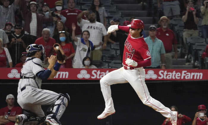 Los Angeles Angels designated hitter Shohei Ohtani, right, avoids a tag by Houston Astros catcher Jason Castro but misses the plate during the 10th inning of a baseball game in Anaheim, Calif., on Sept. 22, 2021. Ohtani was later tagged out by Castro. (AP Photo/Mark J. Terrill)